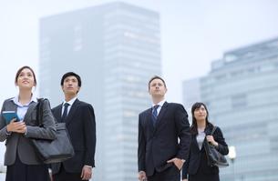 オフィスビルを背景に上を見上げて立つビジネス男女の写真素材 [FYI02967908]