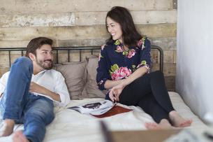 ベッドの上で談笑する男性と女性の写真素材 [FYI02967912]