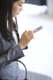 スマートフォンを見るビジネス女性の横顔の写真素材 [FYI02967914]