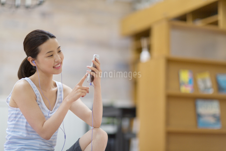 スマートフォンで音楽を楽しむ女性の写真素材 [FYI02967915]