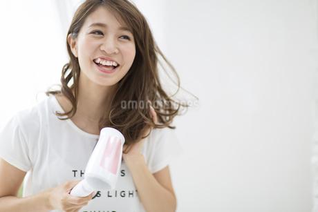 ドライヤーで髪を乾かす女性の写真素材 [FYI02967920]