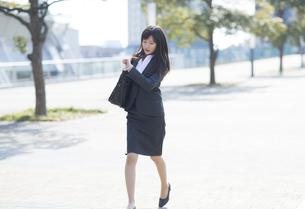 時計を見ながら走るビジネス女性の写真素材 [FYI02967922]