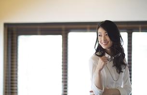 オフィスで眼鏡を手に持ち微笑むビジネス女性の写真素材 [FYI02967924]