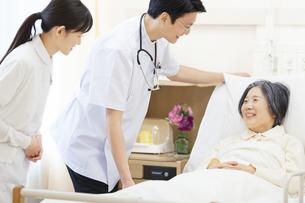 ベッドの患者を診察する男性医師と女性看護師の写真素材 [FYI02967927]