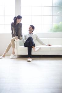 ソファーに座って微笑む男性と女性の写真素材 [FYI02967928]
