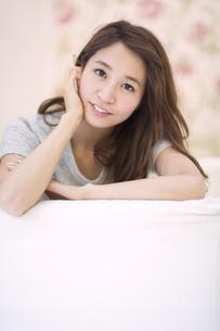 ソファに寄り掛かって微笑む女性のポートレートの写真素材 [FYI02967932]