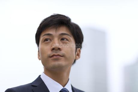 オフィスビルを背景に上を見上げるビジネス男性の写真素材 [FYI02967933]