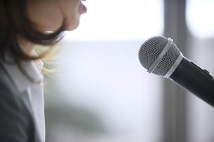 マイクに向かって話すビジネス女性の口元の写真素材 [FYI02967935]
