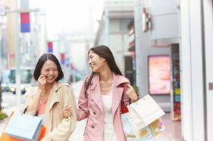買い物中に腕を組んで笑い合う女性二人の写真素材 [FYI02967937]