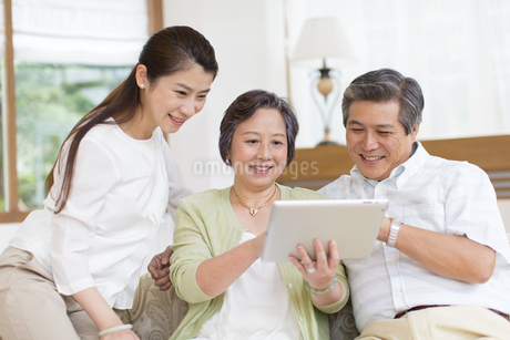 タブレットPCを見るシニア夫婦と娘の写真素材 [FYI02967940]