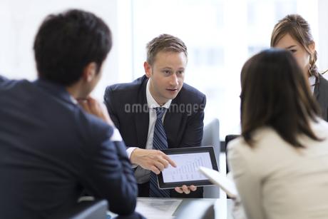 タブレットPCを持ち打ち合せをするビジネス男女の写真素材 [FYI02967944]