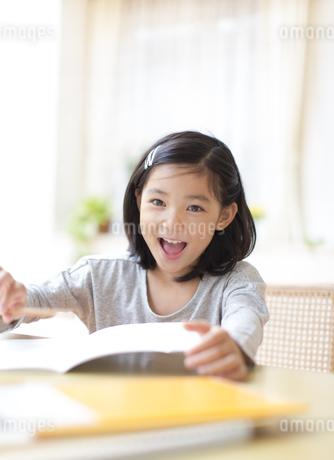 ノートを前に笑う女の子の写真素材 [FYI02967948]