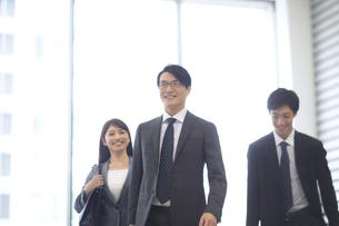 オフィスビルのロビーで微笑むビジネス男女の写真素材 [FYI02967951]