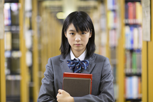 図書室で本を抱える女子高校生の写真素材 [FYI02967952]