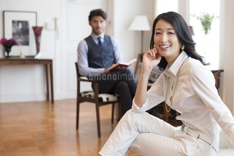 ソファーに座って微笑む女性と椅子に座って本を持つ男性の写真素材 [FYI02967954]