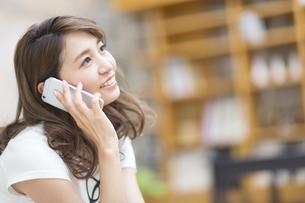 遠くを眺めて電話をかける女性の写真素材 [FYI02967955]