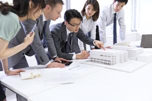 会議室で建築模型を使って打ち合せをするビジネス男女の写真素材 [FYI02967958]