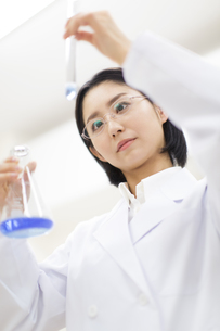 フラスコと試験管を使って研究をしている女性研究員の写真素材 [FYI02967960]