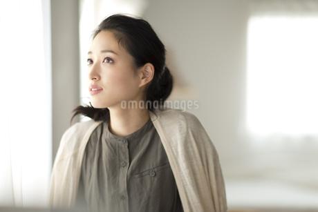 窓際で上を見上げる女性の写真素材 [FYI02967962]