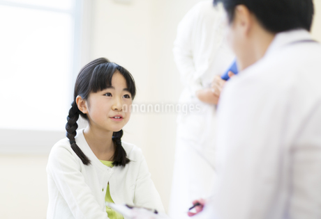 男性医師に問診されている女の子の写真素材 [FYI02967964]