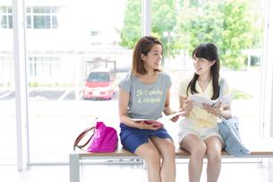 腰かけて話す2人の女子学生の写真素材 [FYI02967966]
