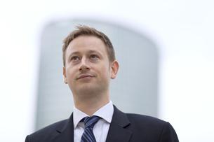 オフィスビルを背景に上を見上げるビジネス男性の写真素材 [FYI02967967]