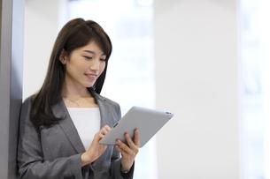 オフィスでタブレットPCを見るビジネス女性の写真素材 [FYI02967969]