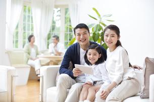 会話する祖父母とソファに掛けて笑顔の親子の写真素材 [FYI02967972]