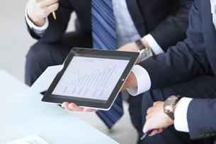 タブレットPCを持ち打ち合せをするビジネス男性の手元の写真素材 [FYI02967973]