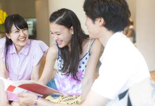 参考書を見ながら談笑する学生たちの写真素材 [FYI02967975]