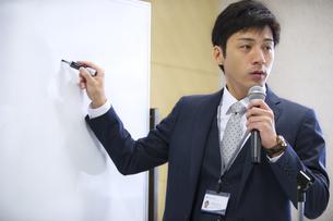 マイクを手に講義するビジネス男性の写真素材 [FYI02967982]