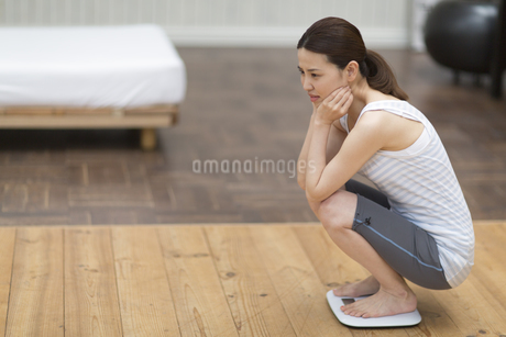 体重計に乗って落ちこむ女性の写真素材 [FYI02967987]