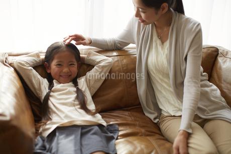 ソファーで寝そべって笑う女の子と頭をなでる母の写真素材 [FYI02967991]