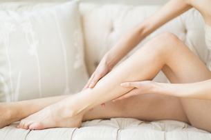 脚のふくらはぎをマッサージをする女性の手元の写真素材 [FYI02967993]
