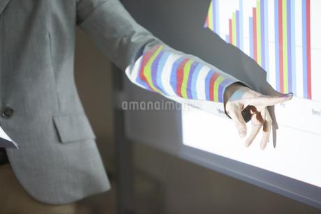 会議でグラフの説明をするビジネス女性の手の写真素材 [FYI02967995]