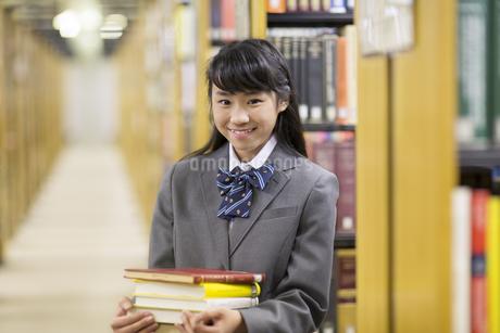図書室で重ねた本を持って笑う女子高校生の写真素材 [FYI02967998]