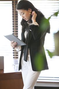 オフィスでタブレットPCを見るビジネス女性の写真素材 [FYI02968002]