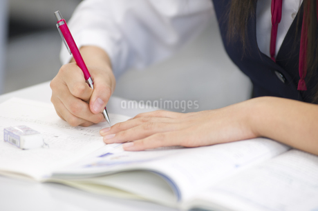 ノートに文字を書く女子学生の手元の写真素材 [FYI02968007]