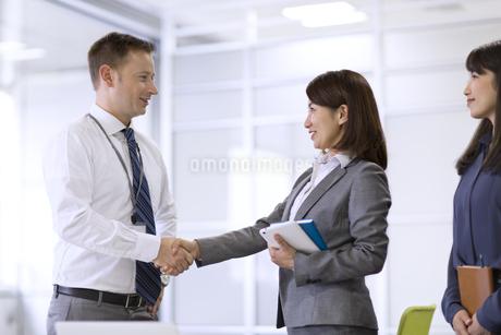オフィスで握手を交わすビジネス男女の写真素材 [FYI02968009]