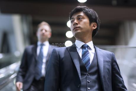 エスカレーターを降りるビジネス男性の写真素材 [FYI02968010]