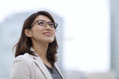 オフィスビルを背景に上を見上げるビジネス女性の写真素材 [FYI02968012]