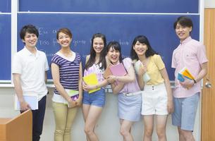 黒板の前に笑顔で並ぶ学生たちのポートレートの写真素材 [FYI02968017]
