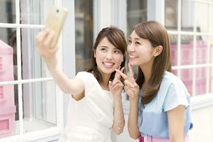 スマートフォンで写真を撮る2人の女性の写真素材 [FYI02968023]