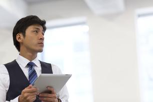 タブレットPCを持ち遠くを眺めるビジネス男性の写真素材 [FYI02968025]