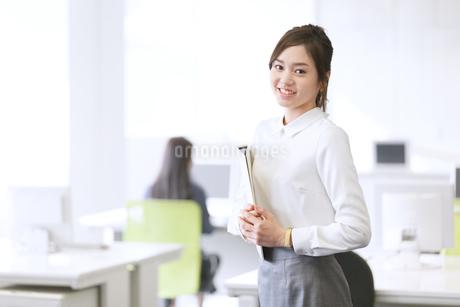 オフィスで資料を持って微笑むビジネス女性の写真素材 [FYI02968028]