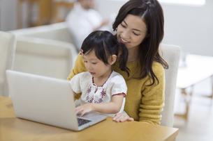 椅子に座ってパソコンを見る親子の写真素材 [FYI02968031]