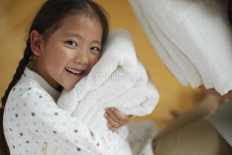 抱いたバスタオルに顔を寄せて笑う女の子の写真素材 [FYI02968032]