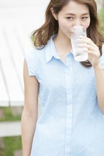 テラスで水を飲む女性の写真素材 [FYI02968033]