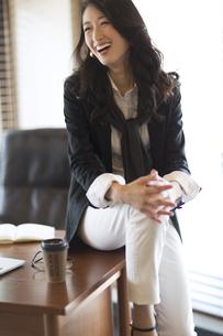 オフィスのデスクに寄りかかり微笑むビジネス女性の写真素材 [FYI02968037]