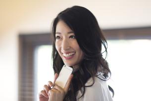 スマートフォンを持って微笑むビジネス女性の写真素材 [FYI02968038]